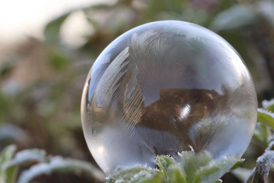 In einer Seifenblase gibt es eine doppelte Spiegelung, so dass das Spiegelbild gerade ausgerichtet ist, im Gegensatz zu der Spiegelung in einer Glaskugel.